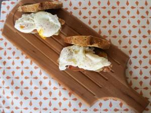 Huevos escalfados sobre jamón y pan