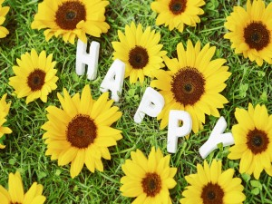 """Postal: """"Feliz"""" entre flores amarillas"""