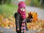 Una niña pequeña recogiendo hojas caídas en otoño