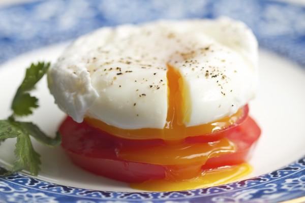 Un huevo poché sobre rodajas de tomate