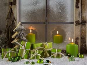 Postal: Velas, pinos, bolas y regalos de color verde junto a una ventana en Navidad