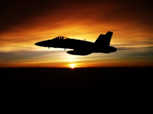 Un avión de combate volando al atardecer
