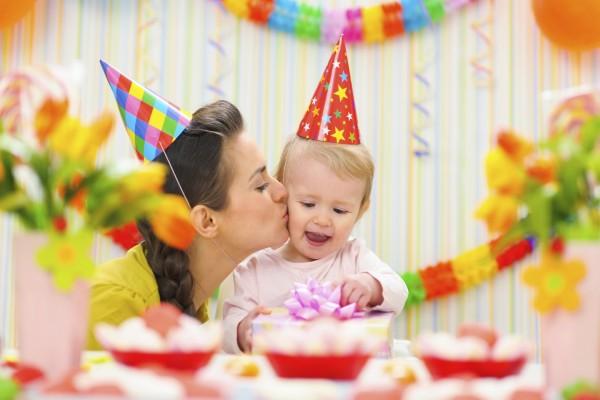 Una madre besando a su bebé en la fiesta cumpleaños