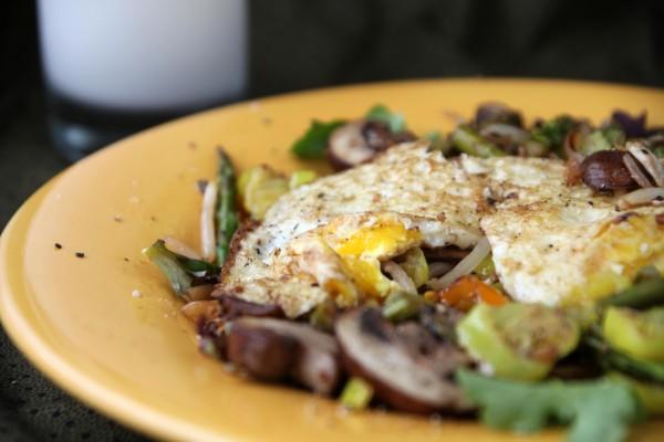 Huevos fritos sobre verduras salteadas
