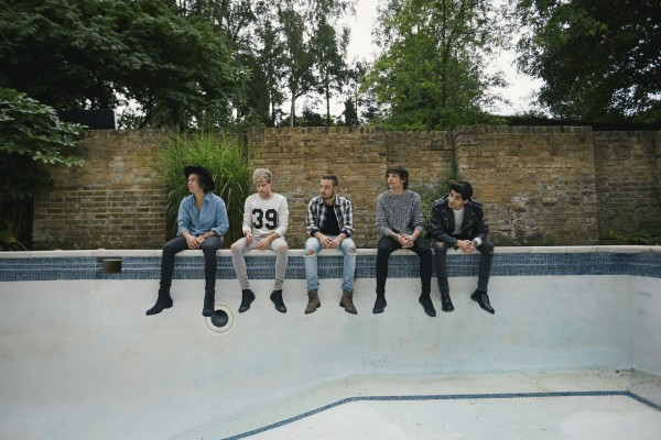 "Los chicos de ""One Direction"" en el bordillo de una piscina"