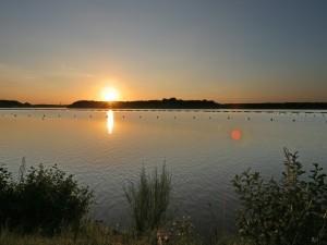 El brillo del atardecer reflejado en el agua