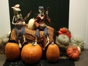 """Postal: Esqueletos sobre calabazas en una decoración para """"Halloween"""""""