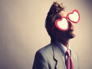 Postal: Un joven enamorado con gafas de corazones