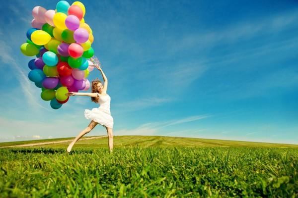 Una joven en un prado con muchos globos de colores