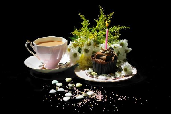 Taza de té junto a una magdalena de cumpleaños y un ramo de margaritas