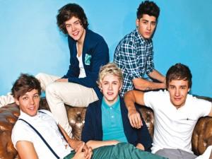 Postal: Los One Direction sentados en un sofá