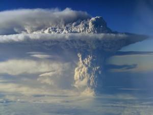 Postal: Densa columna de humo emanando de un volcán en erupción