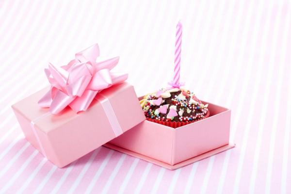 Cupcake con una vela en una cajita rosa de regalo