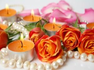 Velas encendidas y rosas naranjas