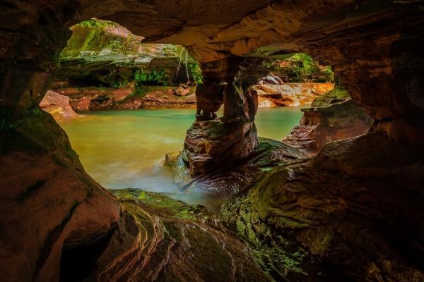 Río que corre entre acantilados y cuevas