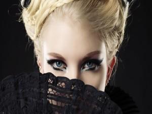 Bella mujer tapando su rostro con un abanico negro