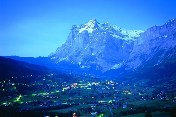 Un pueblo entre montañas iluminado al anochecer