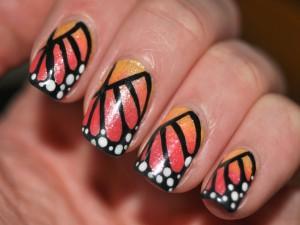 Uñas pintadas con los colores de la mariposa monarca
