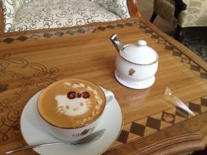 Postal: La cara de Hello Kitty en una taza de café