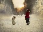 Niña paseando a su perro por la nieve