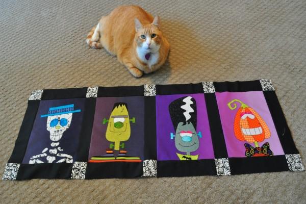 Gato junto a una tela decorada para Halloween