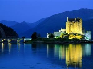 Postal: Un antiguo castillo iluminado al anochecer