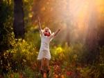 Una niña muy alegre saltando en un bosque otoñal