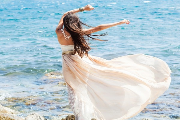 Una mujer con vestido blanco feliz en la playa