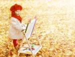 Una bella niña pintando en un espléndido día de otoño