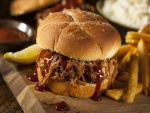 Una hamburguesa con carne desmigada y salsa