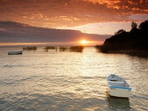 Botes solitarios a la salida del sol