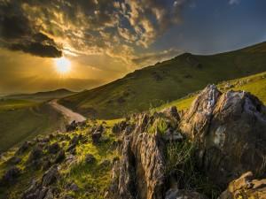 Los rayos del sol al amanecer sobre las colinas y la carretera