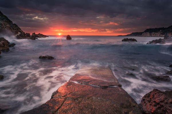 El sol se esconde en el horizonte junto al mar