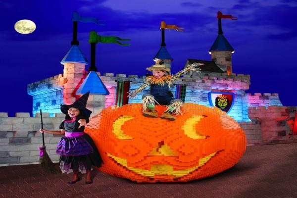 Niños con disfraces para Halloween junto a una calabaza de Lego