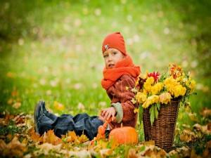 Niña sentada en la hierba en otoño