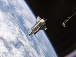 Postal: El transbordador espacial Atlantis y la Tierra