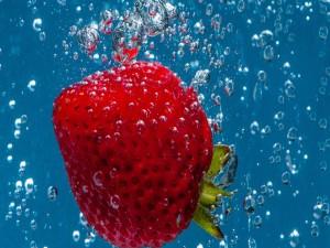 Postal: Fresa en el agua entre burbujas
