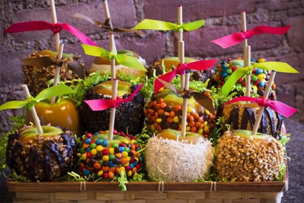 Cesta con manzanas cubiertas de caramelo y otras golosinas