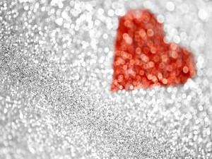 Corazón rojo entre purpurina plateada