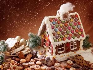 Postal: Galletas y otros dulces navideños junto a una casa de galleta