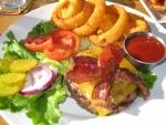 Un plato con ensalada, aros de cebolla y una hamburguesa