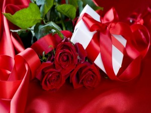 Postal: Caja de regalo junto a un ramo de rosas rojas