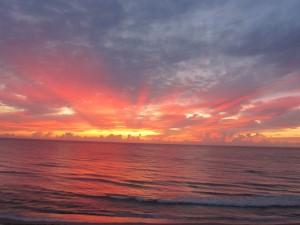Postal: Primeros rayos del sol sobre el mar