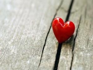 Postal: Un corazón rojo sobre madera