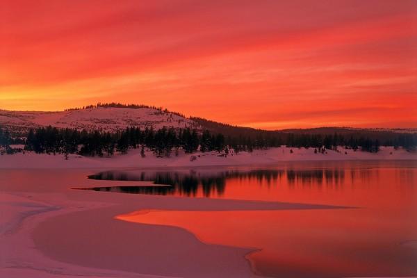 Puesta de sol rojiza sobre un paisaje nevado