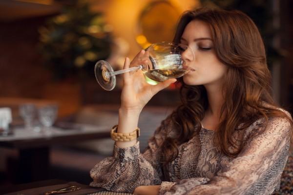 Mujer tomando una copa de vino blanco