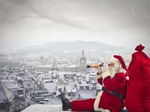 Santa Claus observando una ciudad sentado en un tejado