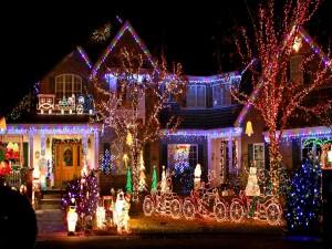 Postal: Luces de Navidad iluminando la casa y las figuras