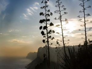 Postal: El sol entre las nubes iluminando los acantilados