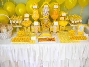 Mesa con caramelos y globos amarillos